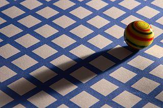 Glasmurmel mit Schatten auf kariertem Grund - Henry Mühlpfordt